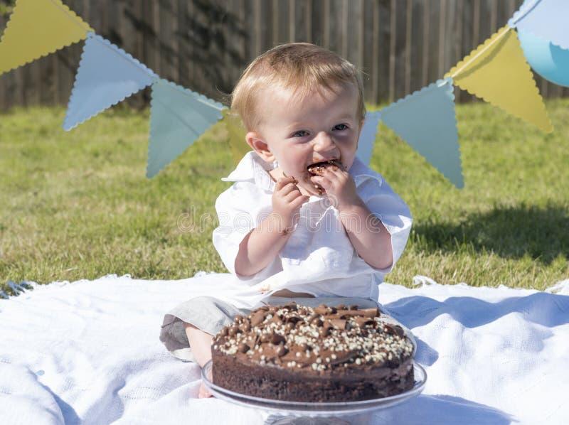 Quebra do bolo de chocolate do bebê do bebê de um ano foto de stock