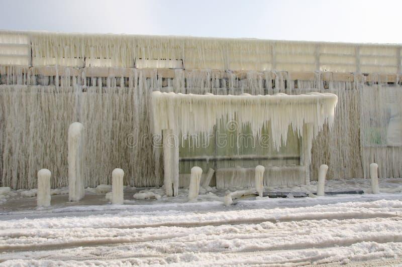 Quebra-mar e paragem do autocarro congelados após a tempestade do inverno imagem de stock