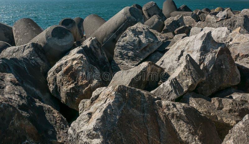 Quebra-mar feito dos pedregulhos, das rochas e do concreto moldado na costa atl?ntica de Portugal imagens de stock royalty free