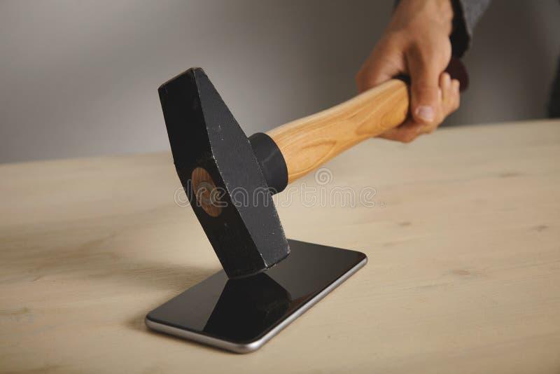 Quebrando o smartphone com um martelo fotografia de stock