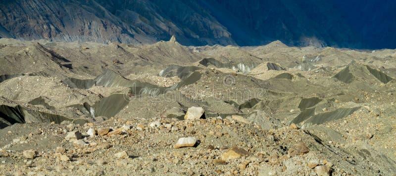 Quebras e gelo da geleira cobertos com as pedras cinzentas do morena imagens de stock royalty free