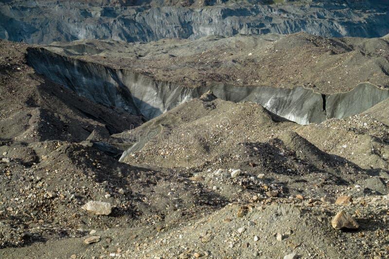 Quebras e gelo da geleira cobertos com as pedras cinzentas do morena foto de stock