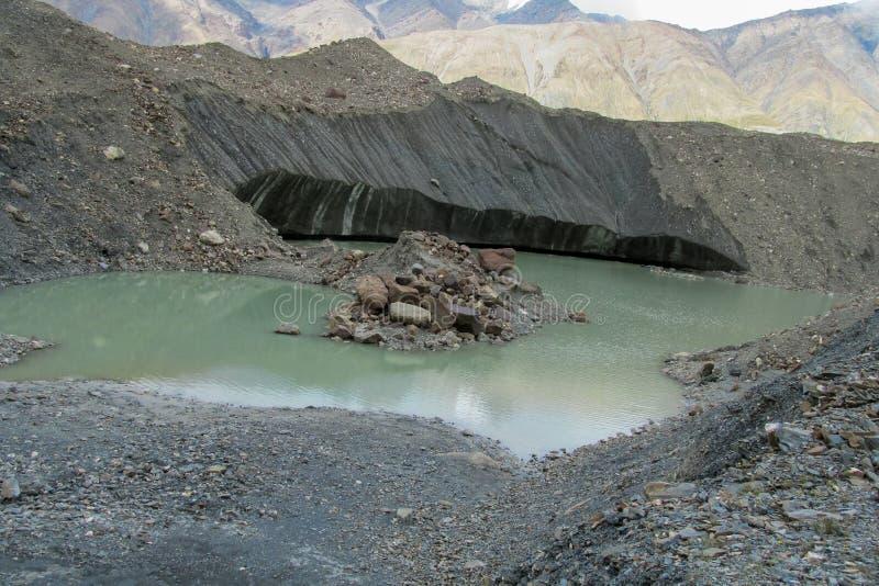Quebras e gelo da geleira cobertos com as pedras cinzentas do morena fotografia de stock
