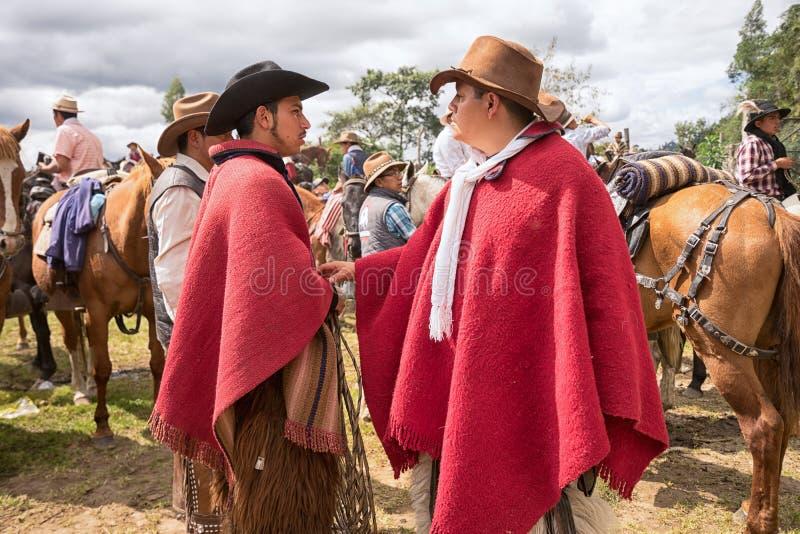 Quechua cowboyer i röd poncho royaltyfri fotografi