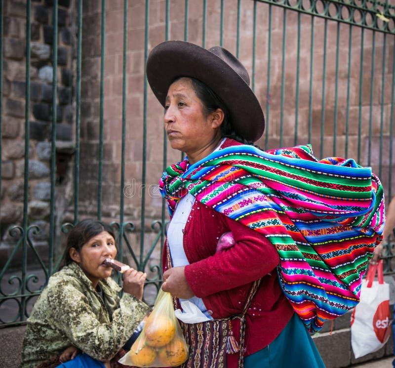 Quechua kvinna med sin kardväska på huvudgatan i Cusco City i Peru arkivbilder