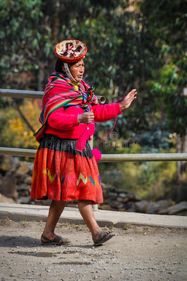 Quechua kvinna som går i en by i Anderna, Ollantaytambo, royaltyfria bilder