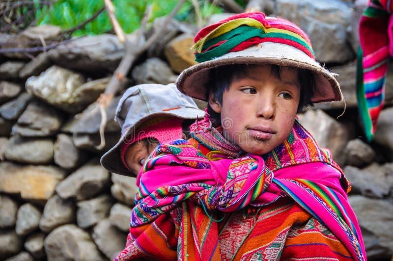 Quechua pojke med systern i en by i Anderna, Ollantaytambo arkivfoto