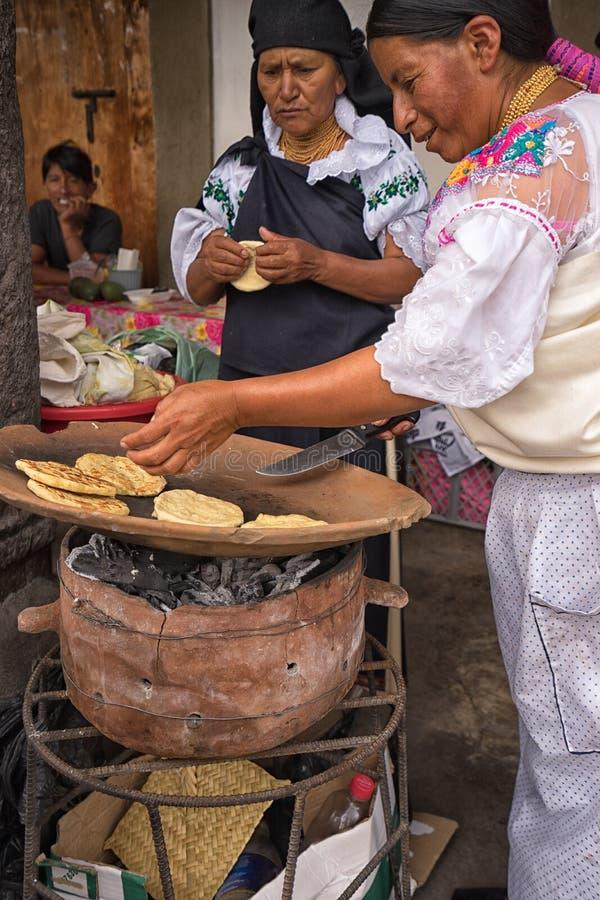 Quechua vrouwen die flatbread op ceramische schotel in Ecuador voorbereidingen treffen stock foto's
