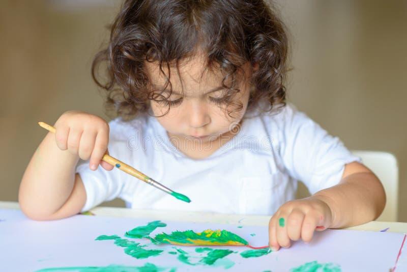 A queda adorável da pintura da criança sae na tabela fotografia de stock