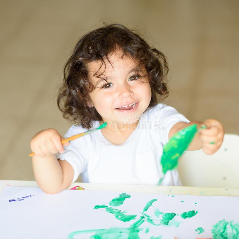 A queda adorável da pintura da criança sae na tabela foto de stock