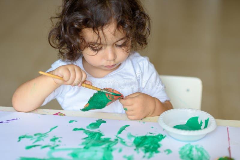 A queda adorável da pintura da criança sae na tabela fotos de stock