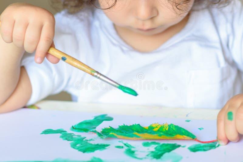 A queda adorável da pintura da criança sae na tabela imagens de stock royalty free
