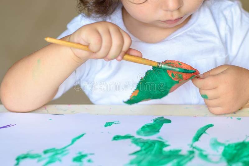 A queda adorável da pintura da criança sae na tabela imagens de stock