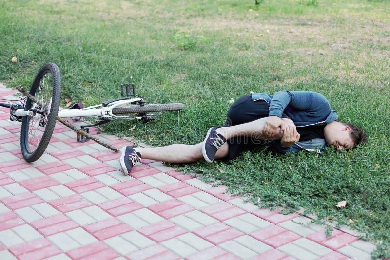 Queda da bicicleta no parque natural O homem caucasiano novo caiu a bicicleta na terra Acidente com uma vara em uma roda imagens de stock