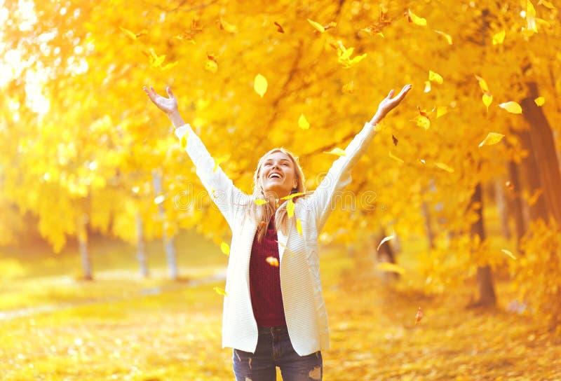 Queda da folha, jovem mulher feliz da expressão que tem o divertimento no outono ensolarado morno foto de stock royalty free