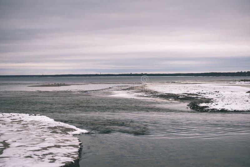 a queda de neve perto do mar no inverno com branco acena o esmagamento - vintage imagens de stock royalty free