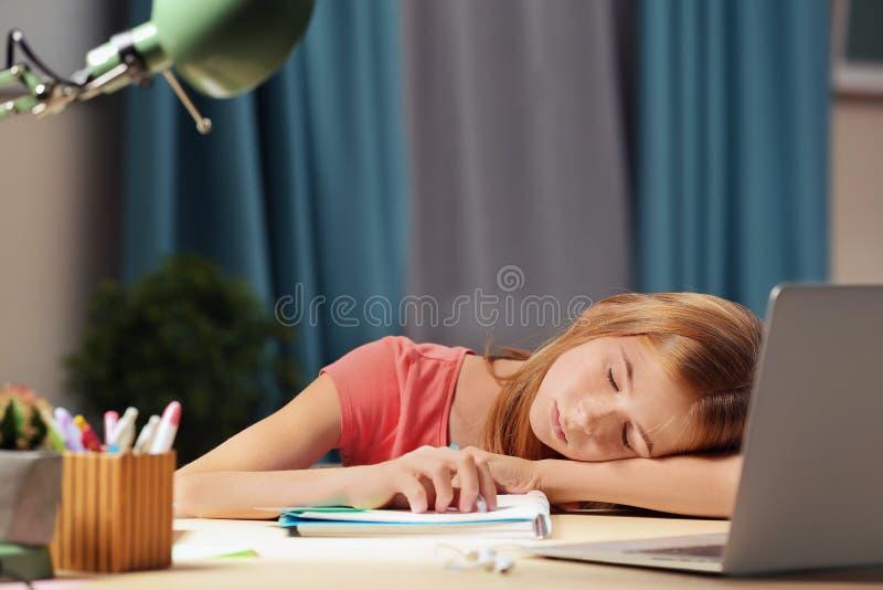 Queda do adolescente adormecida ao fazer trabalhos de casa imagem de stock