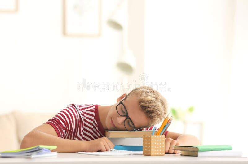 Queda do adolescente adormecida ao fazer trabalhos de casa na tabela fotografia de stock