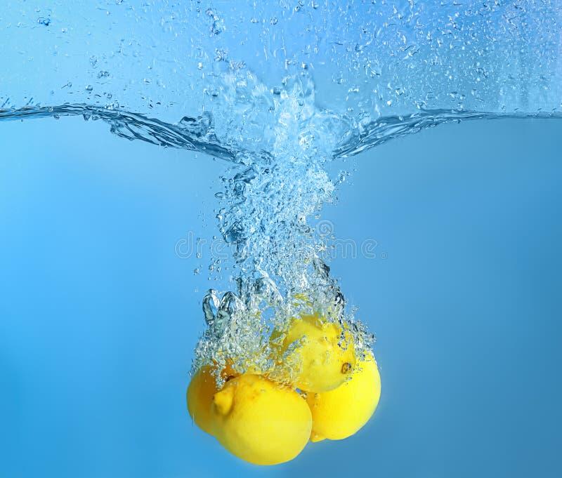 Queda dos limões na água no fundo da cor fotografia de stock royalty free