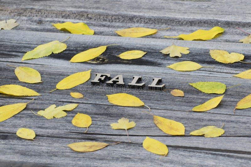 Queda em um fundo de madeira, quadro da inscrição das folhas amarelas fotografia de stock