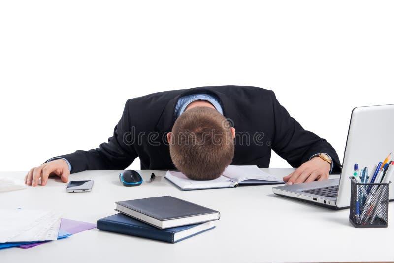 Queda esgotada do homem de negócios adormecida em sua mesa de escritório fotos de stock royalty free