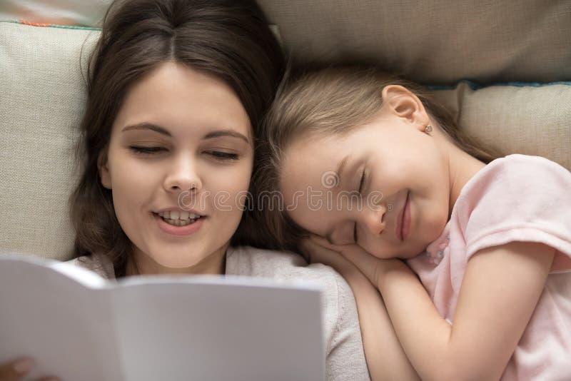 Queda feliz da menina adormecida no livro de leitura do mum da cama fotos de stock