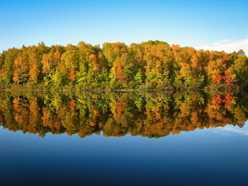 A queda luxúria coloriu a reflexão das árvores na água azul do lago fotografia de stock royalty free