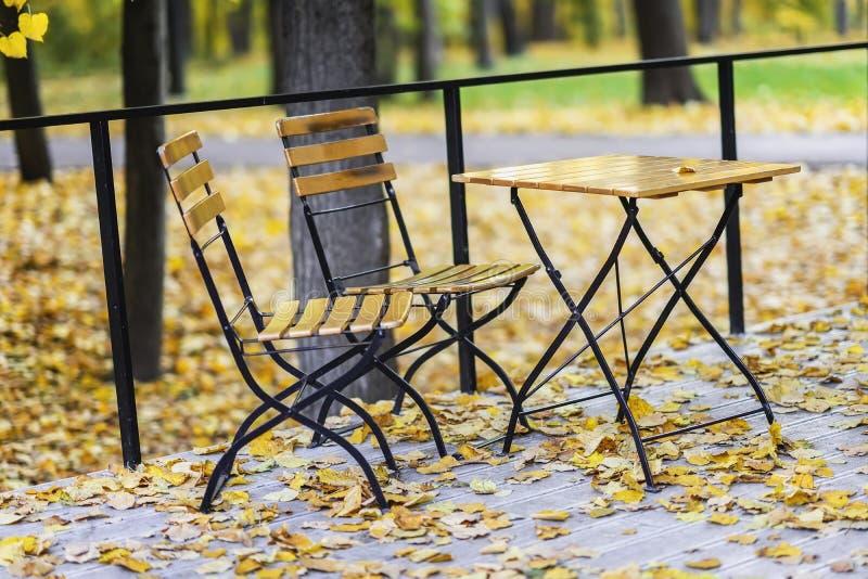 Queda Tabela e cadeiras de madeira no parque vazio do outono, folhas de bordo caídas Conceito do humor do outono fotos de stock