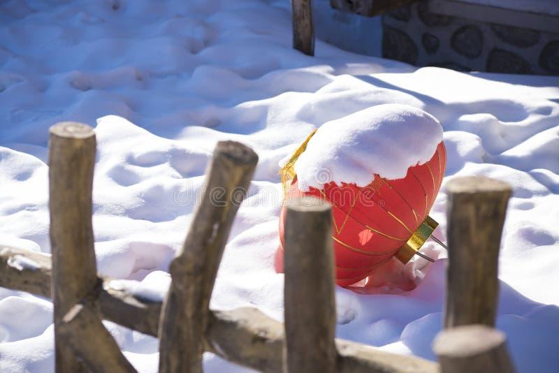 Queda vermelha chinesa decorativa da lanterna na neve branca pura na cidade da neve de China, fora no fundo rural velho do bathho fotografia de stock