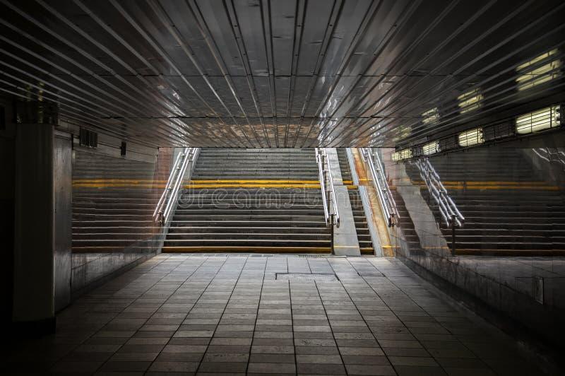 Quedas da luz solar na saída das escadas de uma passagem subterrânea da rua imagens de stock