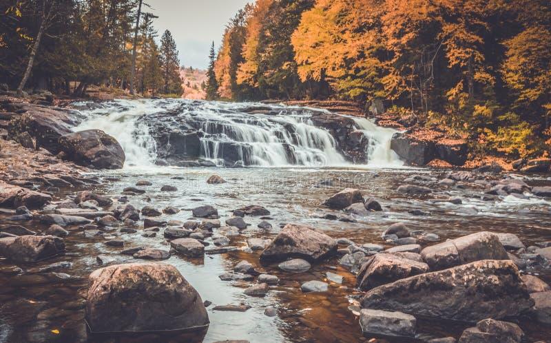 Quedas do soro de leite coalhado cercadas pela folhagem de outono brilhante no lago longo NY, montanhas de ADK fotografia de stock royalty free