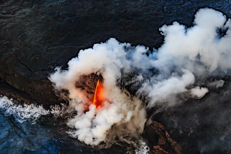 Quedas quentes da lava no Oceano Pacífico que causa explosões e gás imagens de stock