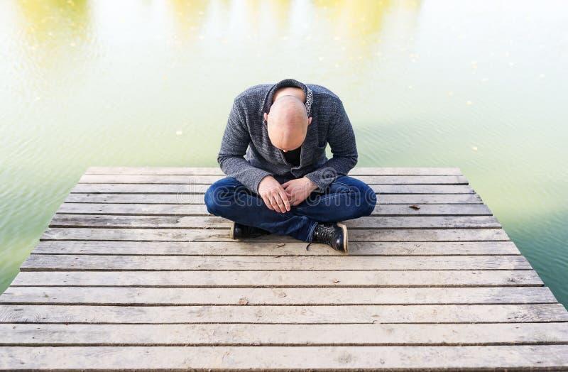Quedese calvo al hombre joven que se sienta en el embarcadero en el parque y meditar foto de archivo libre de regalías