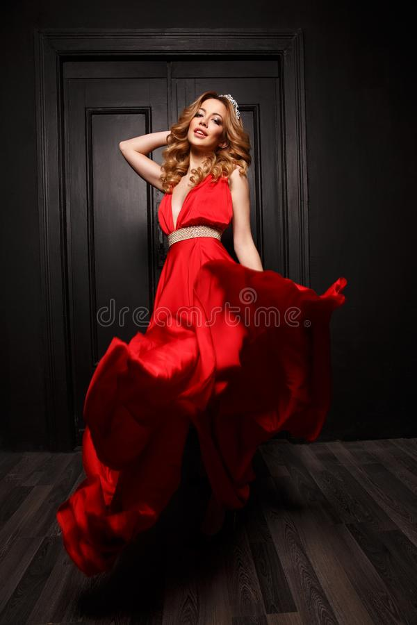 The queen of the ball with diadem on her head is very passionate and stunning in the elegant red evening fluttering dress royalty free stock photography