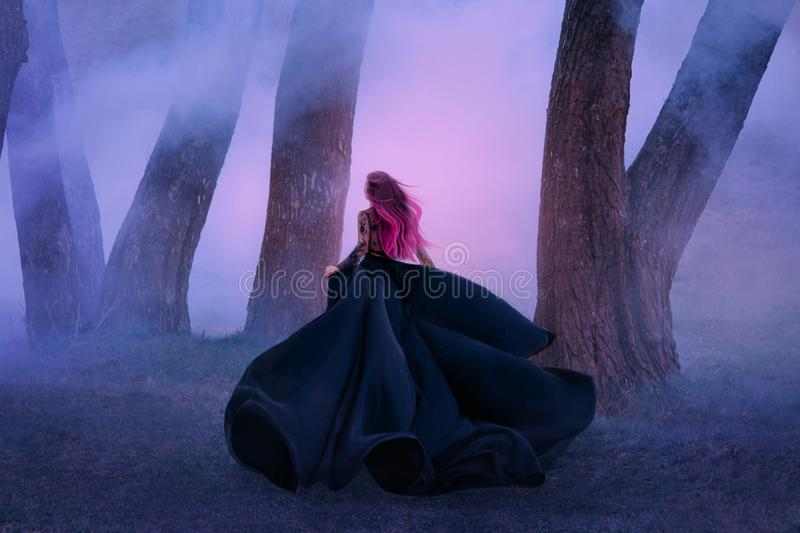 The queen in black dress, runs away in the fog. The skirt train is waving in the wind like a black flower. Pink long royalty free stock photos