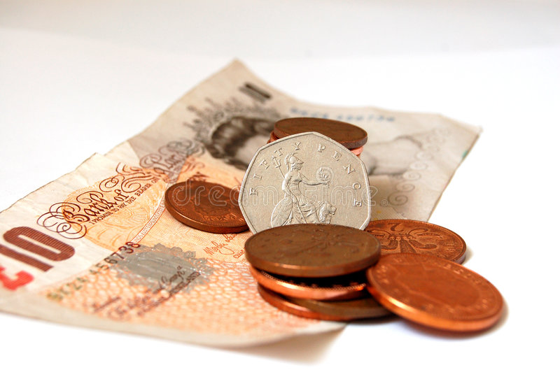 Queen of coins. Fifty pence standing tall amongst, coppers and ten pound note royalty free stock photos