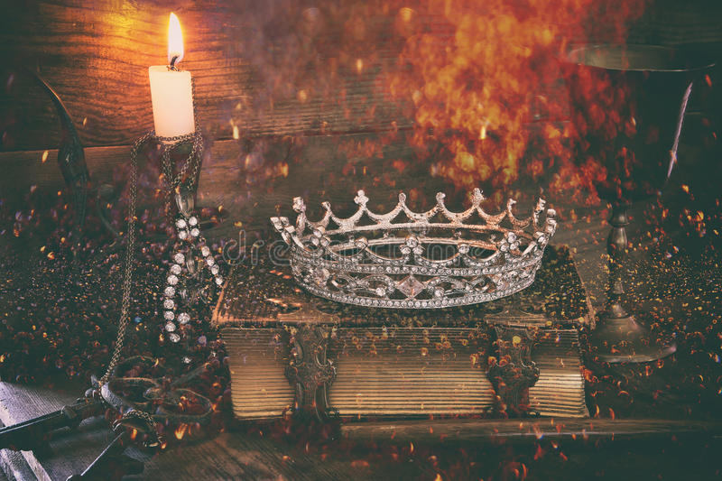 Queen crown on old book. fantasy middle age concept. Abstract low key image of beautiful diamond queen crown on old book, burning candle. vintage filtered with royalty free stock photography