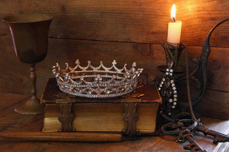 Queen crown on old book. fantasy middle age concept. Low key image of beautiful diamond queen crown on old book, burning candle. vintage filtered. fantasy middle royalty free stock photo