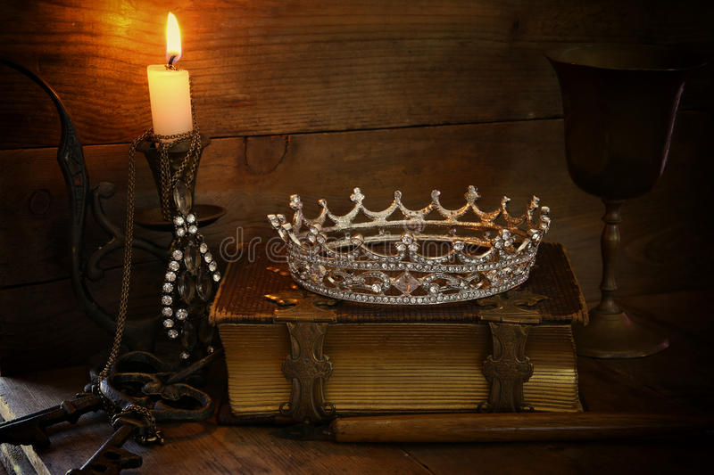 Queen crown on old book. fantasy middle age concept. Low key image of beautiful diamond queen crown on old book, burning candle. vintage filtered. fantasy middle stock photo