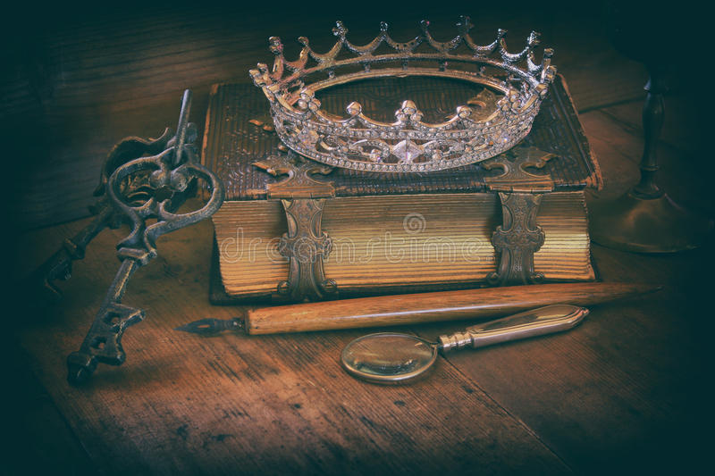 Queen crown on old book. fantasy middle age concept. Low key image of beautiful diamond queen crown on old book. vintage filtered and toned. fantasy middle age royalty free stock photo