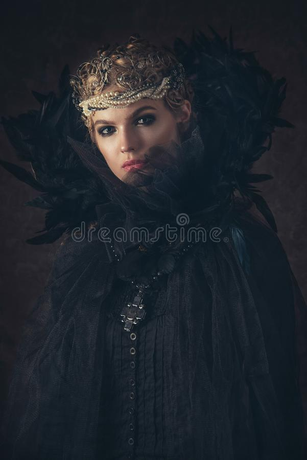 Queen of darkness in black fantasy costume on dark gothic background. High fashion beauty model with dark makeup. Queen of darkness in black fantasy costume on royalty free stock photos