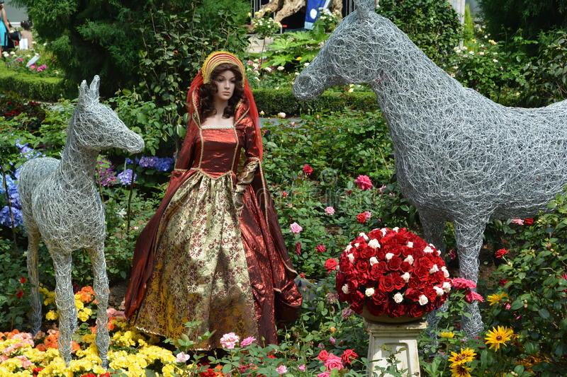 Queen doll in royal gown. Queen doll in between metallic horses and a pot of red roses stock image