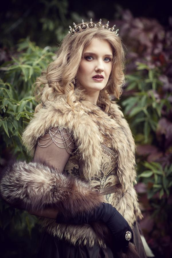 Queen in furs in the autumn forest stock image