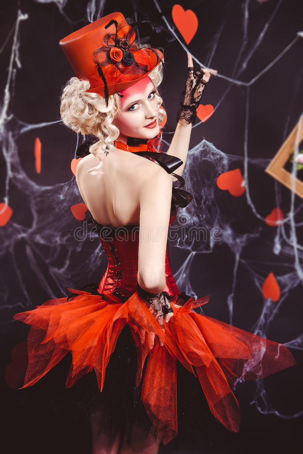 Queen of Hearts. Entered into the real world. Photo shoot in the style of the card game. Unusual, creative make-up, beautiful, funny dress. Vintage hairstyle stock photography