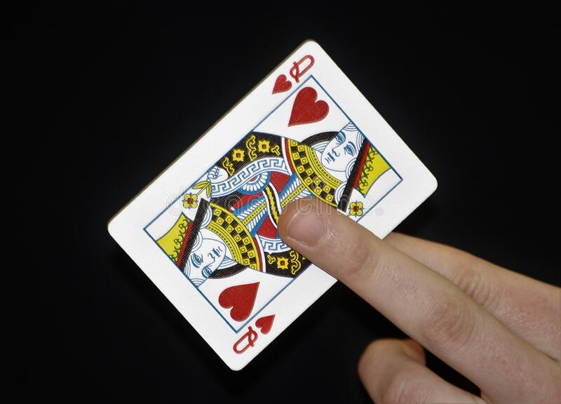 Queen of hearts playing card. Being held up against a black background stock photo