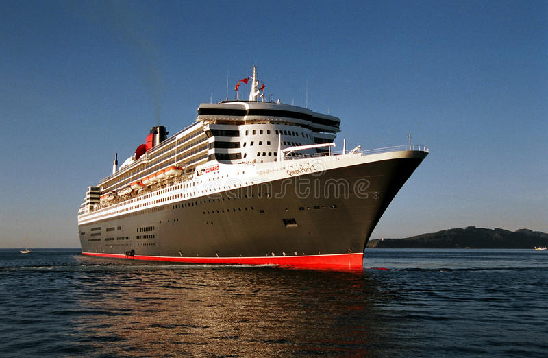 RMS Queen Mary 2 at sea at sunrise. The famous ocean liner RMS Queen Mary 2 at sea in Vigo, Spain in early morning stock photo