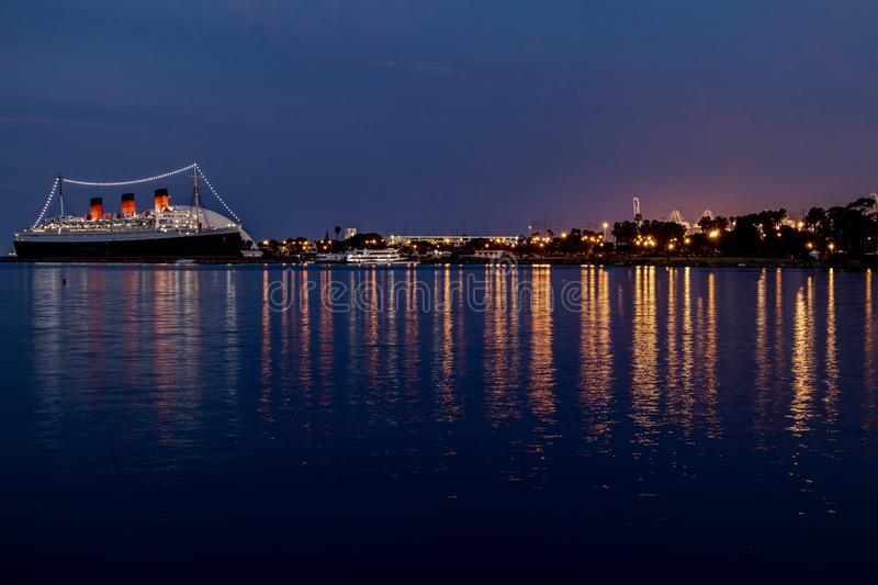 The Queen Mary Ship and city lights in Long Beach, California. Long exposure night time view of The Queen Mary and the city lights.  Lights reflecting off the stock image