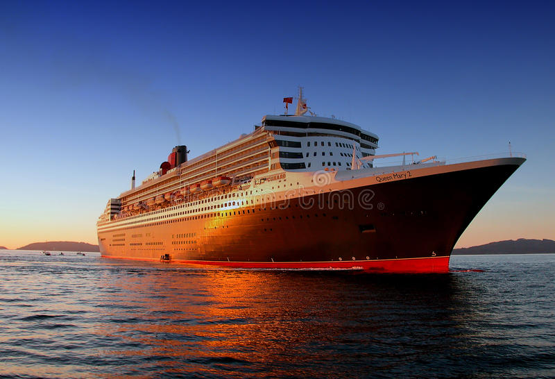RMS Queen Mary 2 on sea in Vigo. The RMS Queen Mary 2 ocean liner on the sea at Vigo, Spain at sunset stock photo