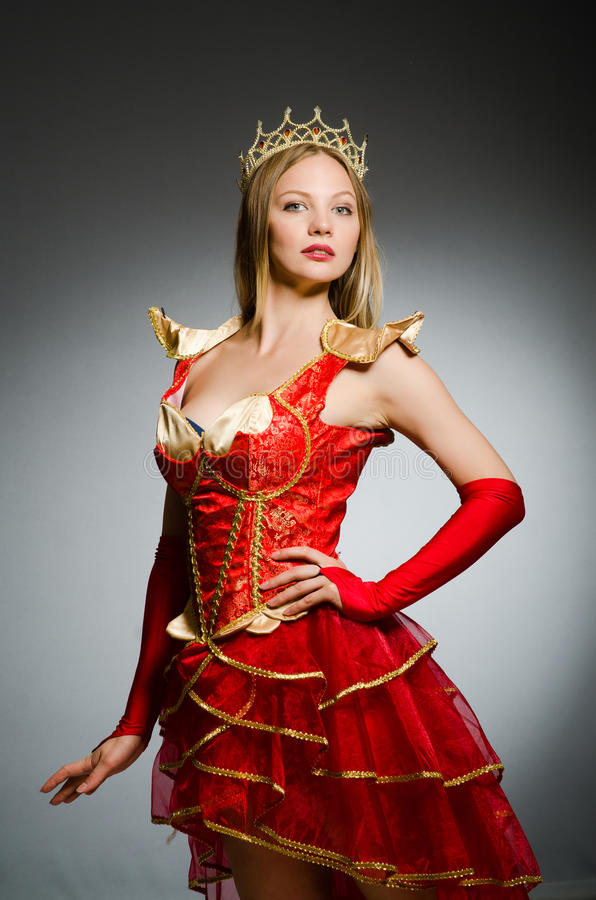 Queen in red costume. Against dark background stock images
