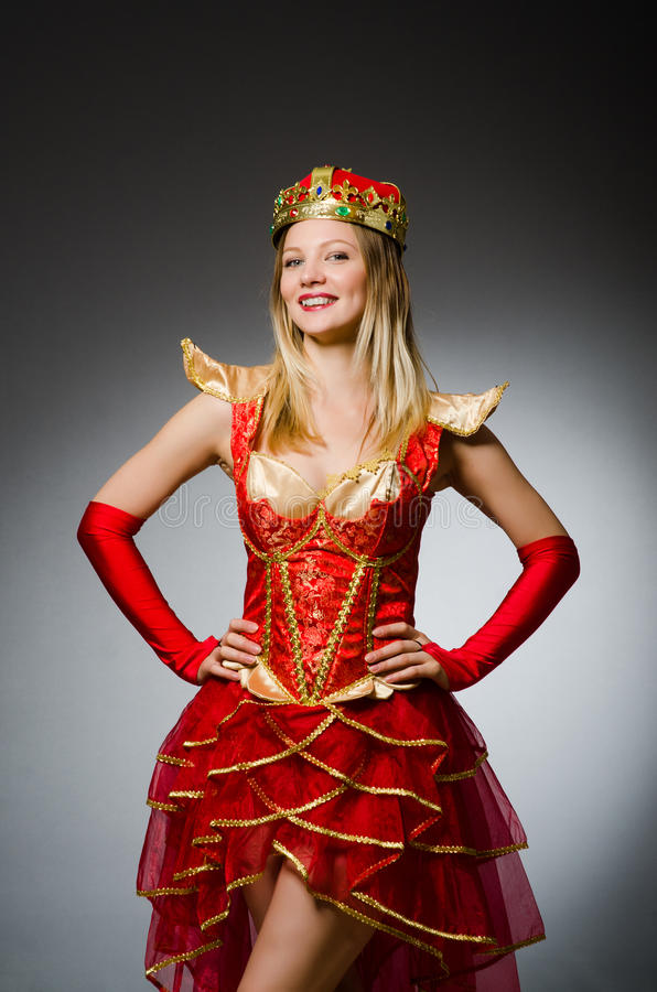 Queen in red costume against. Dark background royalty free stock photography